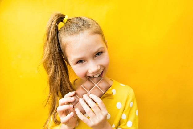 Ragazza teenager felice con barretta di cioccolato e bel sorriso