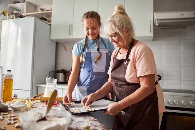 Adolescente felice che aiuta sua nonna in cucina