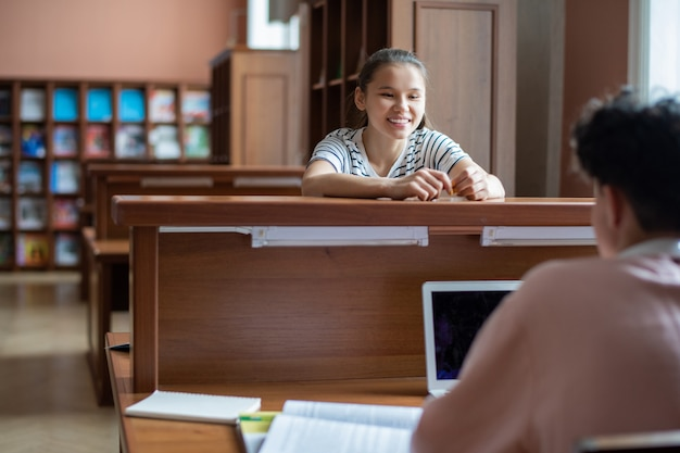 Felice ragazza adolescente guardando il suo compagno di classe con il laptop durante la conversazione nella biblioteca del college dopo le lezioni