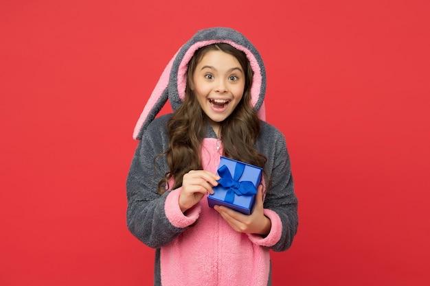 Adolescente felice indossa un pigiama kigurumi di coniglio divertente e tiene in mano una confezione regalo, venerdì nero.