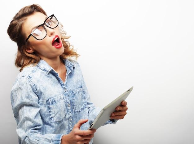 Felice ragazza adolescente con gli occhiali con computer tablet pc