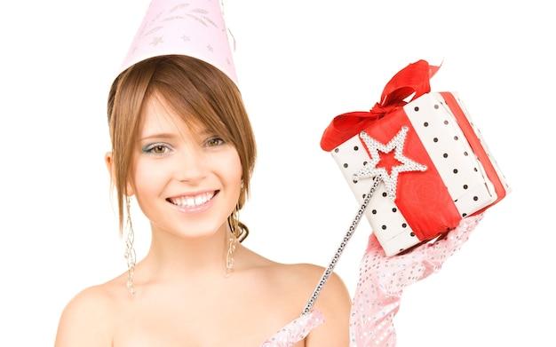 Felice ragazza festaiola con bacchetta magica e confezione regalo