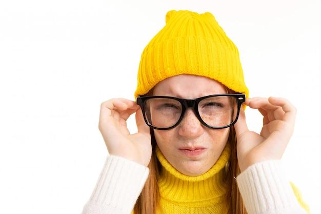 Ragazza felice dell'adolescente con capelli, la maglia con cappuccio e il cappello rossi con i vetri isolati su bianco