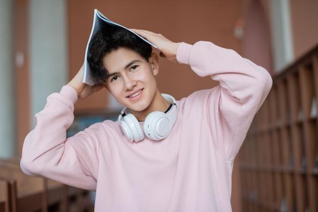 Felice adolescente tenendo il quaderno sopra la testa mentre posa
