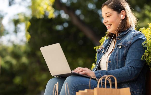 Adolescente felice che tiene il suo laptop all'aperto