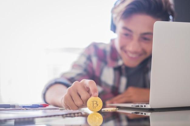 Adolescente felice con cuffie e laptop che giocano con bitcoin