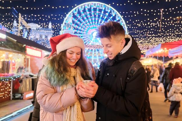 Gli adolescenti felici coppia un ragazzo e una ragazza in cappello della santa al mercatino di natale, scaldando le mani con la candela