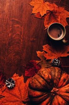 Fondo felice di autunno di ringraziamento con la zucca, i coni, la tazza di caffè e le foglie