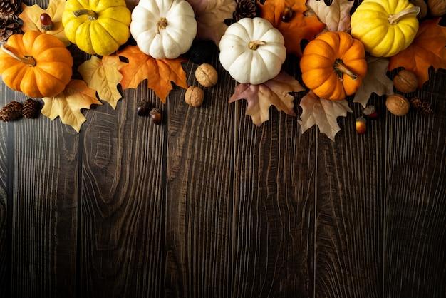Buon giorno del ringraziamento con zucca e noci sul tavolo di legno