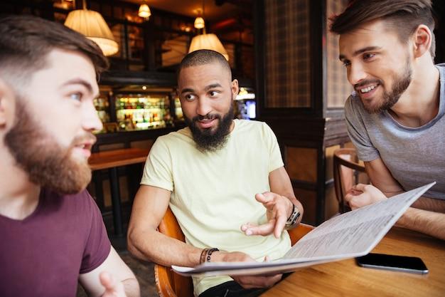 Tre amici maschi felici che leggono il menu nel ristorante