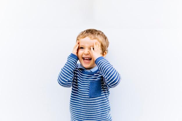 Felice bambino di tre anni sorridente e felice con le mani sul viso