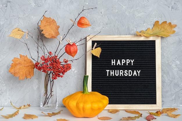 Felice giovedì testo sulla bacheca nera e bouquet di rami con foglie gialle su mollette in vaso