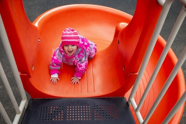 Ragazzo felice del bambino che gioca su una diapositiva in un parco giochi con tempo freddo