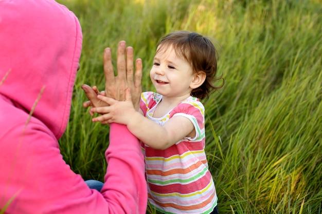 La ragazza felice del bambino batte le mani con il padre nell'erba alta