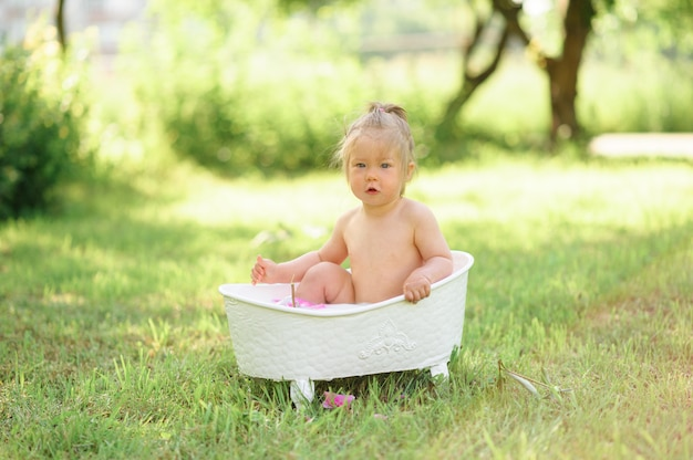 La ragazza felice del bambino prende un bagno del latte con i petali. bambina in un bagno di latte. mazzi di peonie rosa. bagnetto igiene e cura dei bambini piccoli.