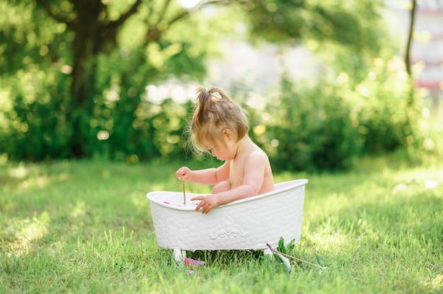 La ragazza felice del bambino prende un bagno del latte con i petali. bambina in un bagno di latte su un verde. mazzi di peonie rosa. bagnetto igiene e cura dei bambini piccoli.