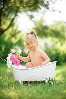 La ragazza felice del bambino prende un bagno del latte con i petali. bambina in un bagno del latte su verde. mazzi di peonie rosa. bagnetto