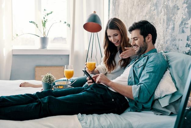 Felici insieme. bella giovane coppia che fa colazione mentre trascorre il tempo a letto a casa