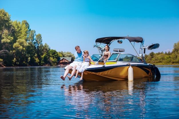 Felici insieme. il giovane padre premuroso e la sua piccola figlia seduti insieme sulla prua della barca mentre la madre li osserva con affetto