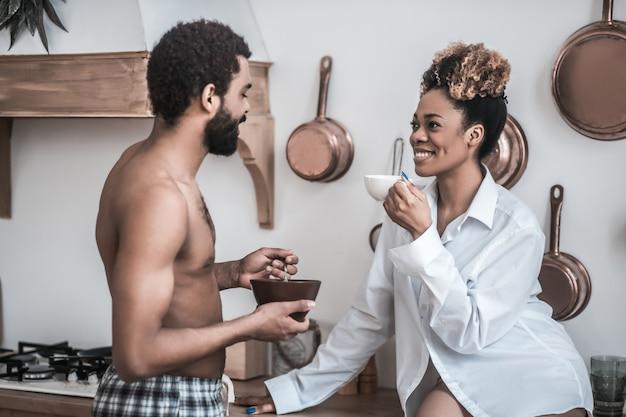 Felici insieme. giovane marito adulto dalla carnagione scura a torso nudo con piatto e moglie in camicia con caffè facendo colazione parlando allegramente in cucina