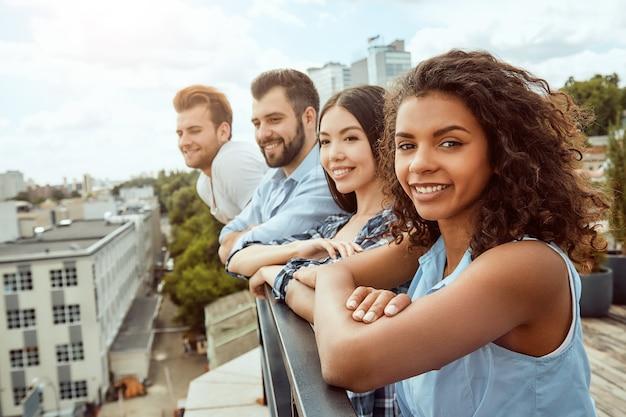 Un gruppo felice di giovani allegri sorride e guarda la città mentre