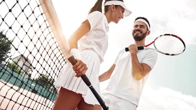 Felice insieme uomo e donna giocheranno a tennis