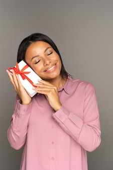 Una giovane donna felice e commossa tiene una confezione regalo sul viso con gli occhi chiusi soddisfatta di un regalo inaspettato