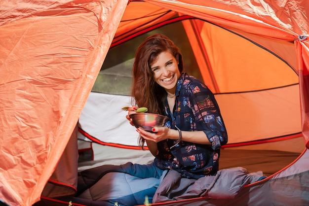 Ragazza turistica felice pranzare in tenda