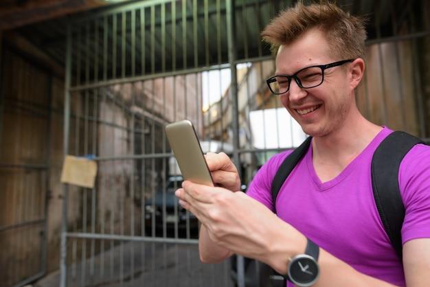Felice turista uomo sorridente e utilizzando il telefono cellulare all'aperto