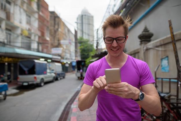 Felice turista uomo sorridente e utilizzando il telefono cellulare in strada all'aperto