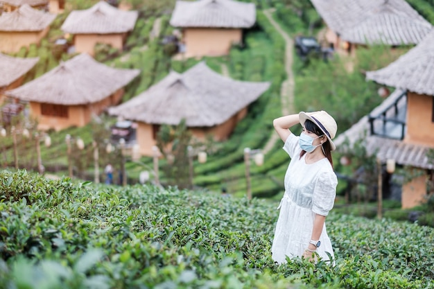 La donna turistica felice che indossa la maschera chirurgica gode del bellissimo giardino del tè