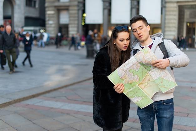 Coppia di turisti felici in possesso di una mappa in una città