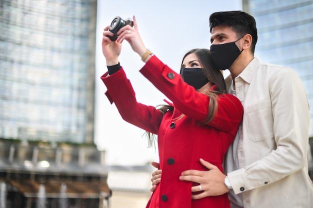 Turisti felici con maschere covid o coronavirus si accoppiano camminando insieme in una città e fotografando un luogo interessante