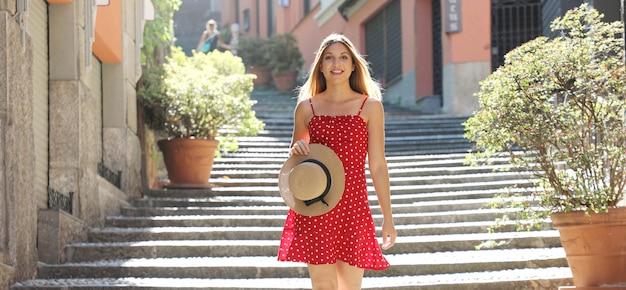 Donna turistica di viaggio felice che va al piano di sotto a bellagio sul lago di como, italia. ragazza in vacanza estiva visitando famosa destinazione turistica in europa.