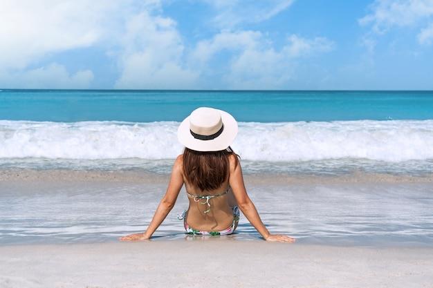 La donna asiatica felice del viaggiatore in bikini gode alla spiaggia tropicale in vacanza. estate sul concetto di spiaggia.