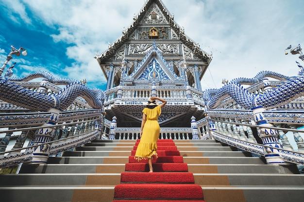 Donna asiatica del viaggiatore felice con il viaggio del vestito nel tempio di wat pak nam khaem nu, chanthaburi, tailandia