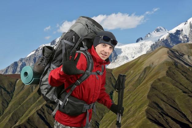 Felice viaggiatore equipaggiato con una giacca rossa sul fianco della collina sollevata in mano salutante