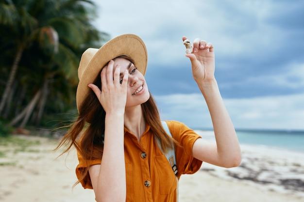 Il viaggiatore felice esamina le conchiglie su un'isola