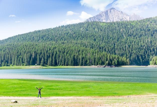 Viaggiatore felice al lago in montagna