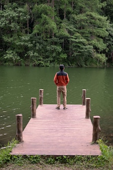 Felice viaggiatore uomo in piedi in un molo e guardando il fiume e lo sfondo della foresta