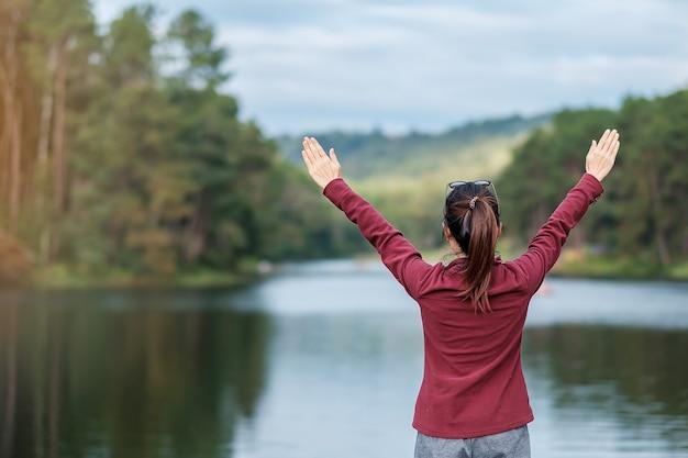 Felice viaggiatore donna vista posteriore con le braccia in alto e guardando uno sfondo di fiume e foresta