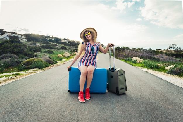 Donna felice del viaggiatore che si siede su una valigia sulla strada e che sorride. concetto di viaggio, viaggio, viaggio.