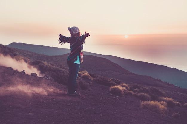 Felice viaggiatrice vista dalla schiena aprendo le braccia per abbracciare la meravigliosa natura fantastica durante il tramonto