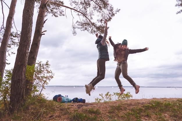 Donne felici viaggiatori saltando.