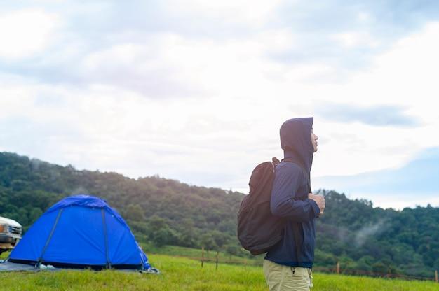Uomo di viaggio felice che gode e si rilassa vicino alla tenda del campo