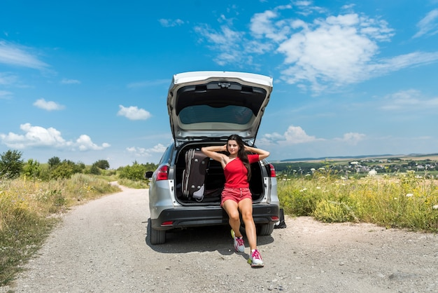 Donna in viaggio felice che si siede nel bagagliaio dell'auto e che riposa sulla fermata in campo rurale. stile di vita estivo
