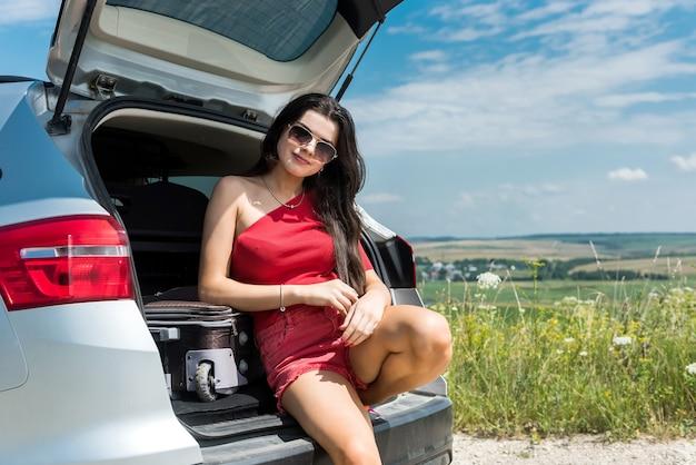 Donna viaggiante felice che si siede nel bagagliaio dell'auto e riposa in sosta in campo rurale stile di vita estivo