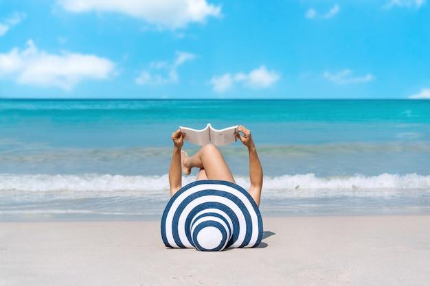 Viaggiatore felice la donna asiatica si sdraia a leggere un libro sulla spiaggia tropicale in vacanza. estate sul concetto di spiaggia.