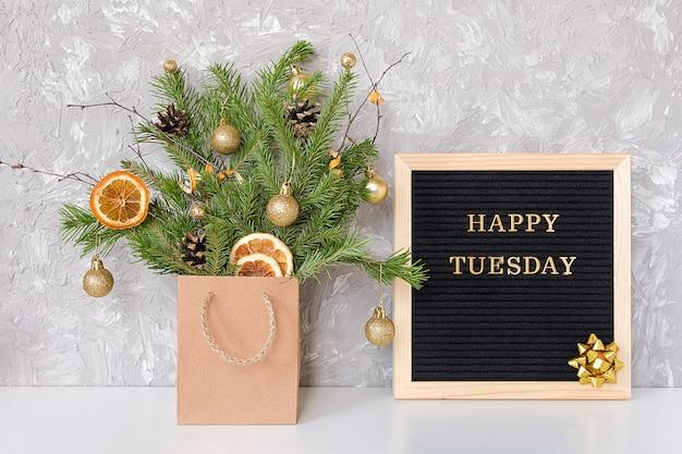 Testo felice di martedì sul bordo di lettera nero e mazzo festivo dei rami dell'abete con la decorazione di natale in pacchetto del mestiere sulla tavola
