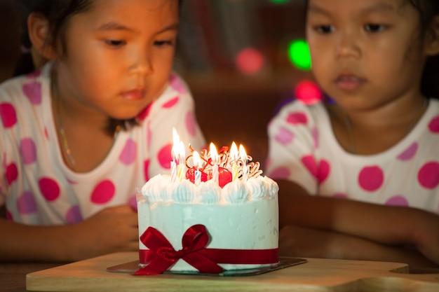Gemelli felici che celebrano il loro compleanno e che soffia insieme le candele
